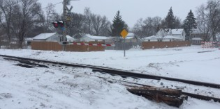 Train drags derailed car through town, tearing up crossings