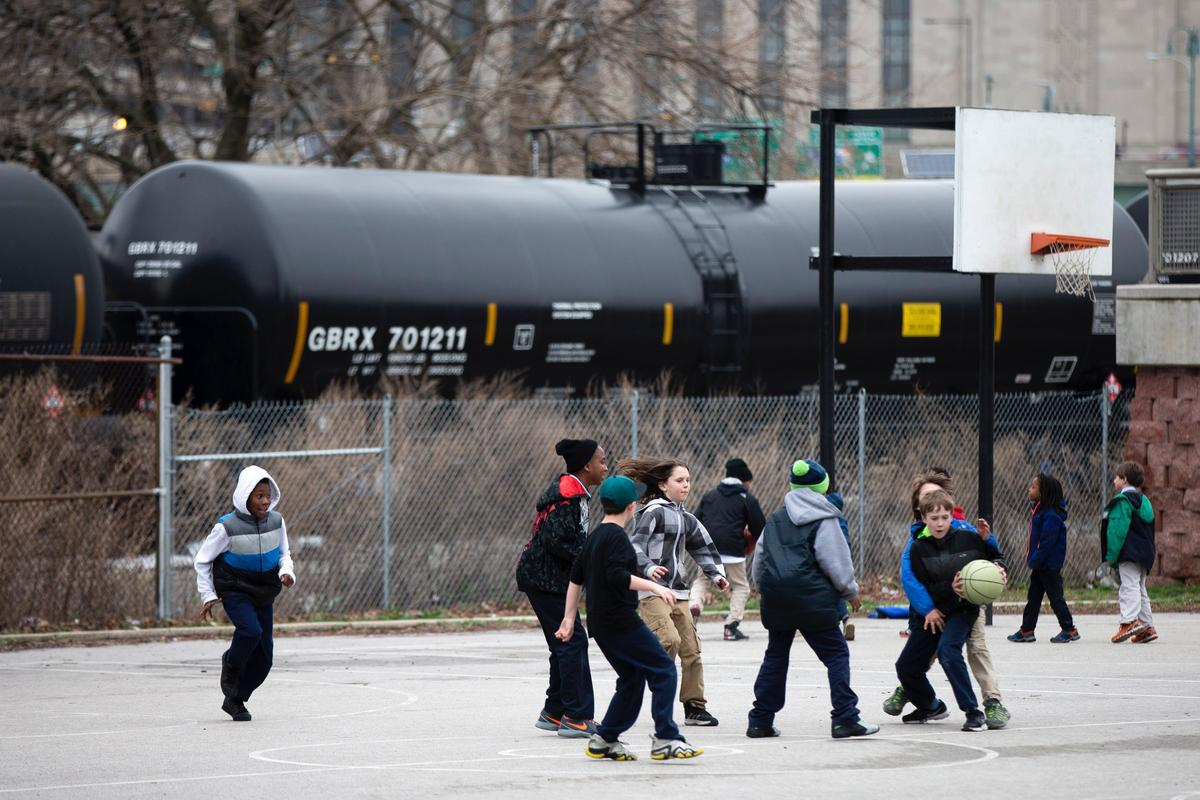 In this photo taken April 9, 2015, children play in view of train tank cars with placards indicating petroleum crude oil standing idle on the tracks, in Philadelphia. Rail tank cars that are used to transport most crude oil and many other flammable liquids will have to be built to stronger standards to reduce the risk of catastrophic train crash and fire under a series of new rules unveiled Friday by U.S. and Canadian transportation officials. (AP Photo/Matt Rourke)